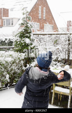 Little girl throws snowballs in a backyard, enjoying the first snow in late autumn, blur from the movement. - Stock Photo