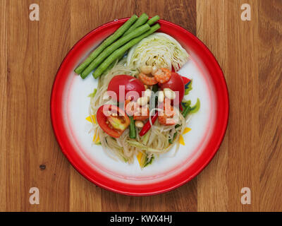 Thai green papaya salad, Som Tam, famous street food of Thailand in traditional floral print tray on wooden background - Stock Photo