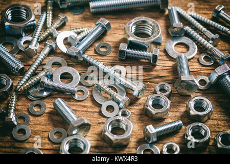 Bolts and nuts on a wooden surface - Stock Photo