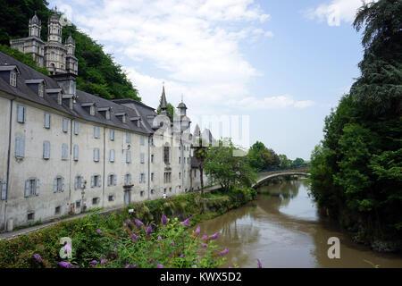 LESTELLE-BETHARRAM, FRANCE - CIRCA JULY 2015 Facade of monastery and bridge on the river - Stock Photo