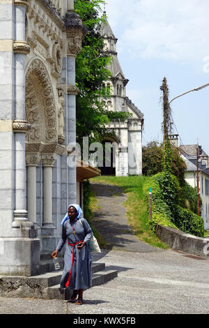 LESTELLE-BETHARRAM, FRANCE - CIRCA JULY 2015 Black nun walk near chapel - Stock Photo