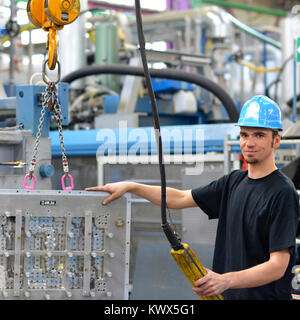 worker operates a crane in an industrial plant - interior in a factory hall - Stock Photo