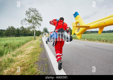 Doctor with defibrillator and other equipment running from helicopter. Teams of the Emergency medical service are - Stock Photo