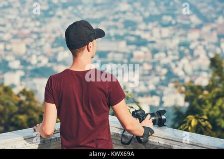 Young photographer (traveler) with photo camera looking for inspiration. Chiang Mai, Thailand - Stock Photo
