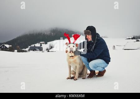 Funny walk with dog in the snowy landscape. Labrador retriever is wearing fake reindeer antlers. Winter season in - Stock Photo