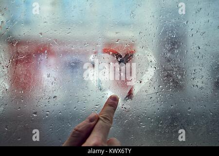 Finger of the young man drawing heart shape on the window with raindrops against city street. - Stock Photo