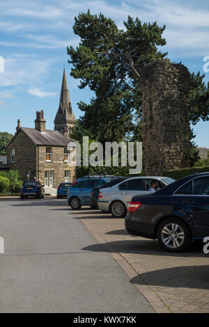 Cars parked in town centre car park by castle ruins on sunny summer day, with tall church spire beyond - Knaresborough, - Stock Photo