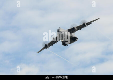 An Airbus A400M Atlas transport aircraft flying towards camera. Visible vortices from wings. - Stock Photo