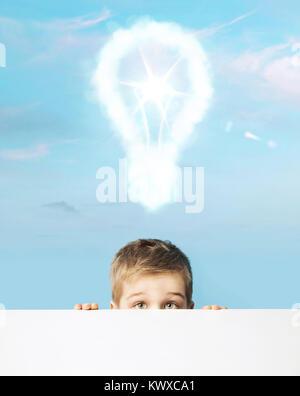 Little boy with a light bulb above head - Stock Photo