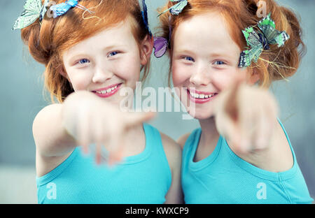 Portrait of two cheerful redhead twin sisters - Stock Photo