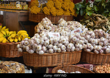 Market stall with a pile of garlic bulbs and other fresh produce on display, Mercado dos Lavradores, Funchal, Madeira, - Stock Photo
