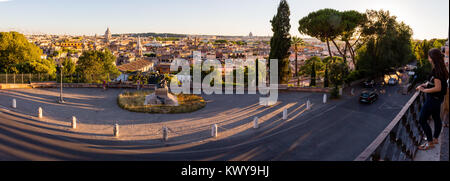 A panorama taken close to sunset of the beautiful city of Rome. Warm sunny light is hitting the roofs of all the - Stock Photo