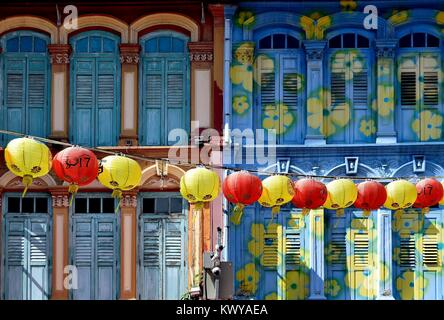 A string of red and yellow lanterns across the retro exterior of traditional Singapore shop houses in Chinatown - Stock Photo