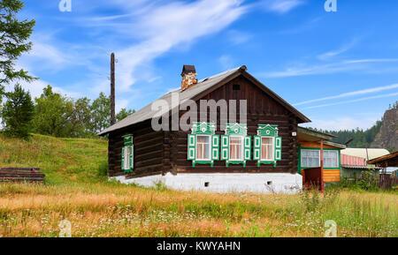 BOLSHIYE KOTY, IRKUTSK REGION, RUSSIA - July 24, 2017: Wooden Russian hut with green shutters on windows. Traditional - Stock Photo