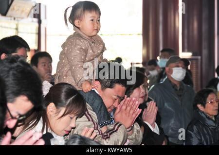 Tokyo, Japan - March 15, 2009: People praying at the Shinto Asakusa Temple in Tokyo, Japan. - Stock Photo
