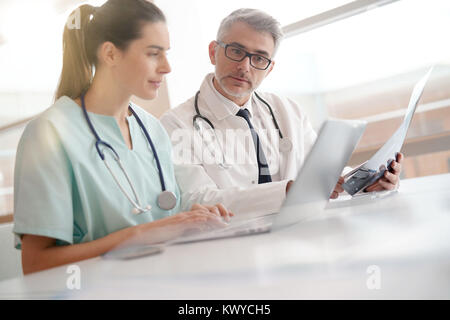 Doctor and nurse in office working on medical report - Stock Photo