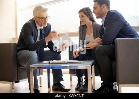 Real-estate agent explaining financial plan to couple buying new home - Stock Photo
