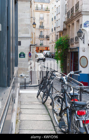 Paris street, view along a typical narrow street near the Rue Des Ursins on the Ile de la Cite with three bicycles - Stock Photo