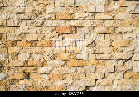 light brown stone brick exterior wall in hard light emphasizing ...