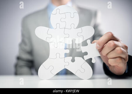 Businessman assembling jigsaw puzzle human team employee concept - Stock Photo