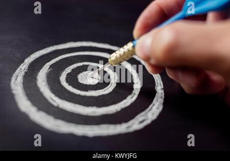 Businessman target for success holding dart on blackboard - Stock Photo