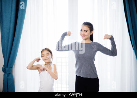 Young woman and charming little daughter are showing their biceps and smiling while working out at home - Stock Photo