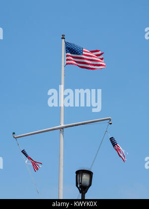 The American flag is flying on top of a flagpole at the port city of Monterey, California - Stock Photo