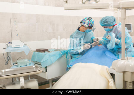 dentist team working with patient. dental surgery. Dentist in mask with loupe binoculars - Stock Photo