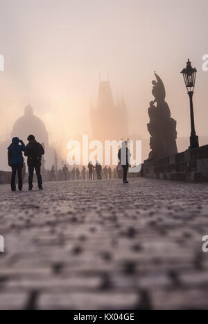 PRAGUE, CZECH REPUBLIC - MARCH 27 2016: Spectators watch the dense fog on Charles Bridge on the bright Easter moring, - Stock Photo