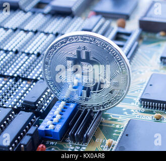 On a printed circuit motherboard is standing silver coin of a digital crypto  currency - Bitcoin. The switch placed - Stock Photo