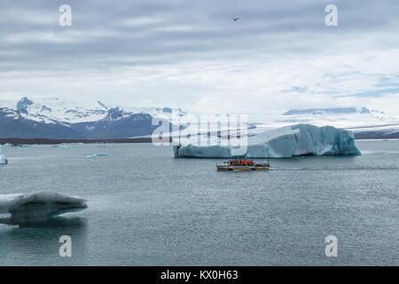 Icebergs and tourist amphibian boat on the Jökulsárlón glacial lagoon calving from the Breiðamerkurjökull Glacier, - Stock Photo
