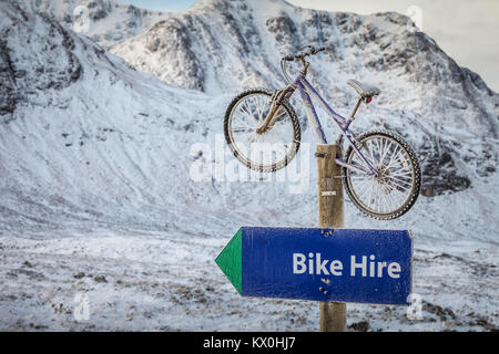 Bike or bicycle on a post advertising cycle hire, Glencoe, Scotland UK - Stock Photo
