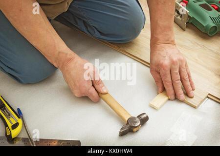 Master works on laying laminate panels, imitating wood - Stock Photo