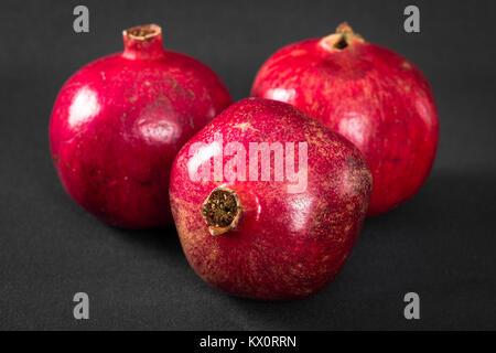 Three ripe pomegranates on a black background Stock Photo