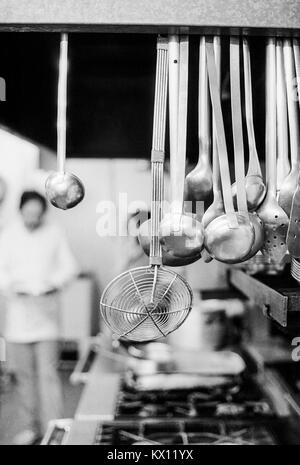 Kitchen utensils hanging over the hobs in a commercial kitchen with blurred background - Stock Photo