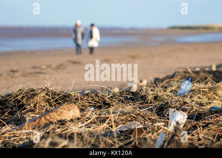 Plastic bottles and beach debris washed up onto the shore line on Southport seafront in Merseyside. - Stock Photo
