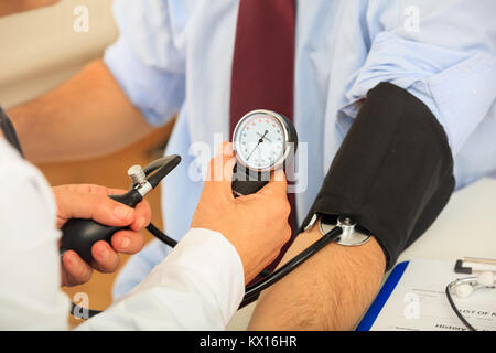 Doctor measuring blood pressure of a patient - Stock Photo
