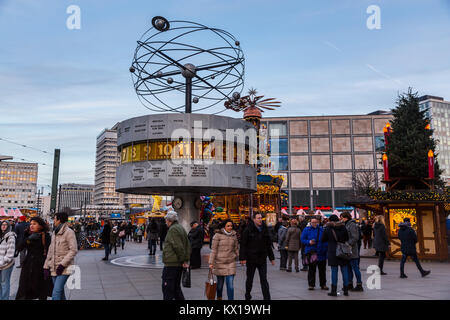 Several tourists are standing under the World Time Clock in Alexanderplatz in Berlin - Stock Photo