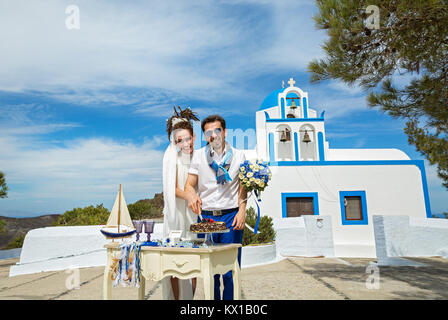 Young couple cuts the wedding cake in the background of the Church building - Stock Photo