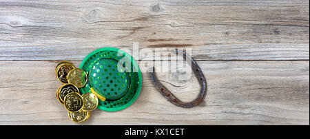Lucky green hat, horseshoe and gold coins for St Patrick on rustic wooden boards in overhead view - Stock Photo