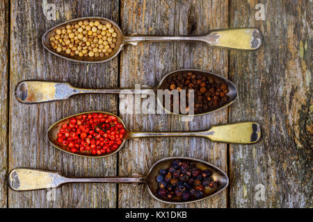 Different types of pepper spice in vintage spoons on wood background different types of spice peppers - Stock Photo
