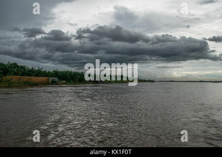 A patch of low dark thick clouds floating over the Mekong river, river bank. Rainy clouds during Monsoon season - Stock Photo