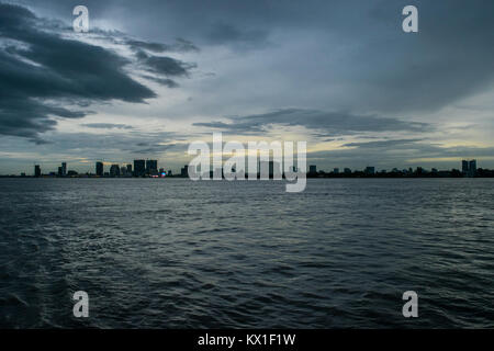Phnom Penh dusk sunset, as seen from the Mekong and Tonle Sap rivers, with emerging sky scrapers. Monsoon season - Stock Photo