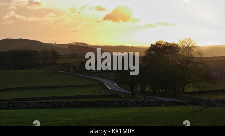 UK Weather: spectacular sunset along the A515 road between Buxton & Ashbourne in the Peak District National Park, - Stock Photo