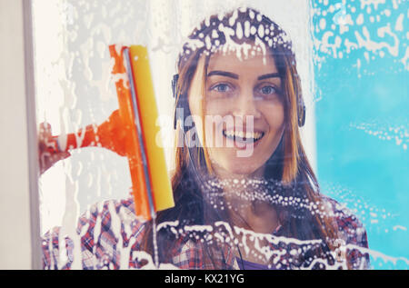 woman cleans the window with a brush - Stock Photo