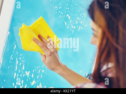 Woman Washing the Window with spray and rag - Stock Photo