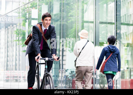 Cheerful young employee riding an utility bicycle in Berlin - Stock Photo