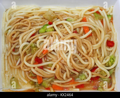 Cardboard container of noodles and vegetables that has been microwaved - Stock Photo