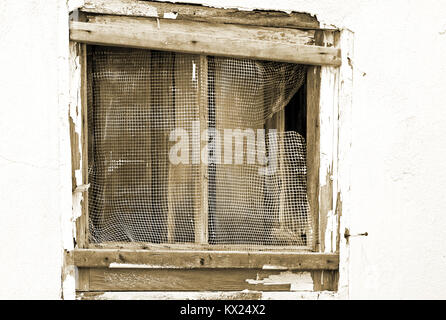 Old run down exterior window and frame in need of repair. Ripped and torn mesh window screen and paint chipping - Stock Photo