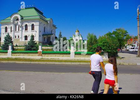Tiraspol, the capital of Pridnestrovye (Transnistria), officially part of Republic of Moldova: A young couple passing - Stock Photo